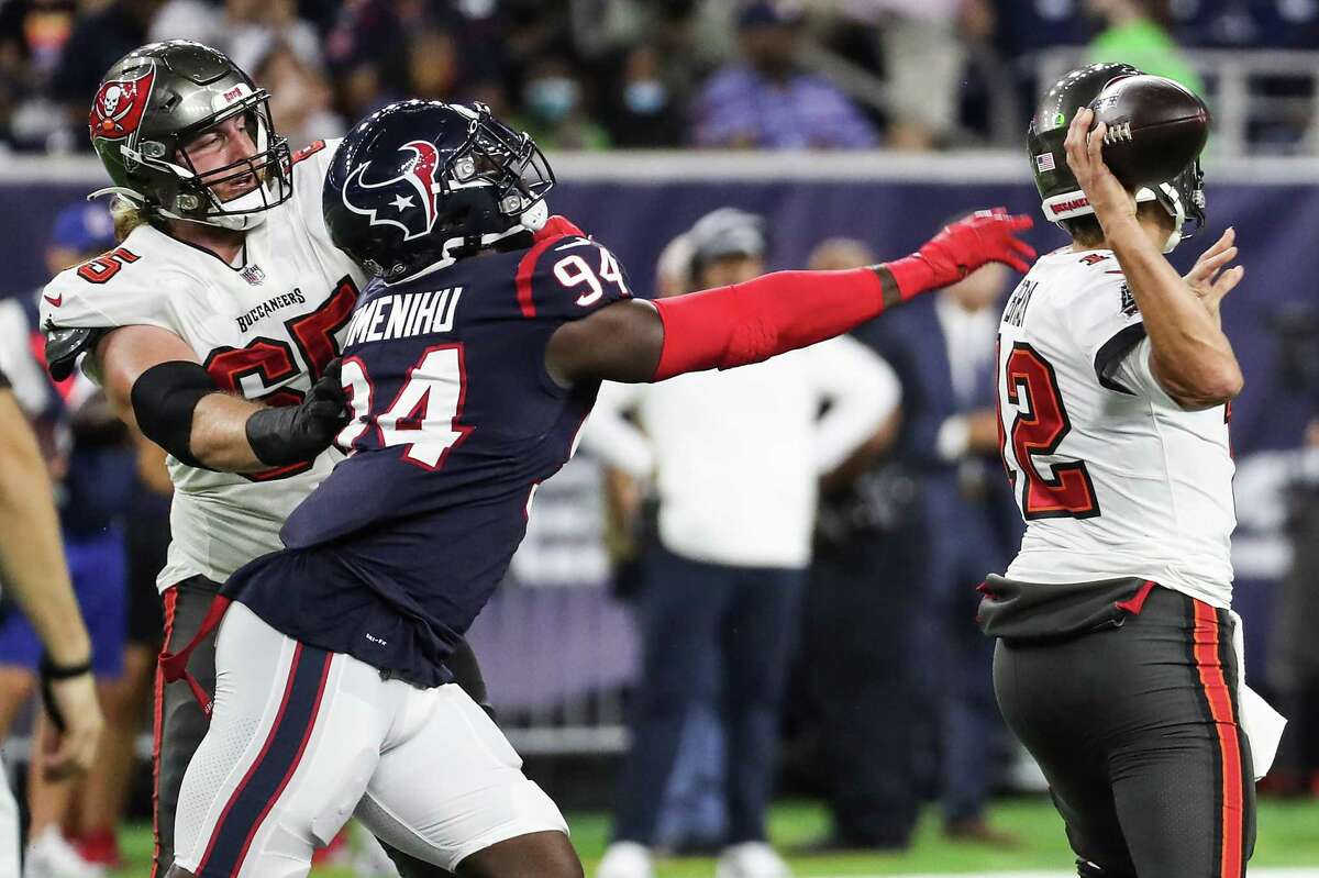 Houston Texans defensive end Charles Omenihu (94) reaches out in vain as Tampa Bay Buccaneers quarterback Tom Brady (12) gets off a pass during the first half of an NFL football game Saturday, Aug. 28, 2021, in Houston.