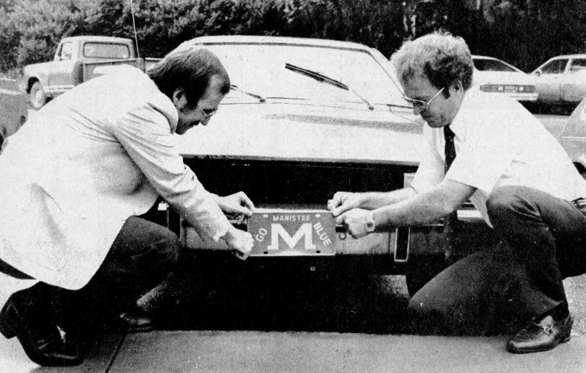"""The Mighty Manistee """"M"""" will be seen on the front of automotive vehicles this fall when the Manistee High School Dad's Club begins selling their decorative front license plates. (From left) Jim Smogoleski of the club and MHS principal Ron Cowden are shown placing a plate on the front of the car. The license plates will be sold at all MHS sporting events. Funds raised from the $3.50 charge per plate will go towardsclub projects. The photo was published in the News Advocate on Aug. 31, 1981. (Manistee County Historical Museum photo)"""