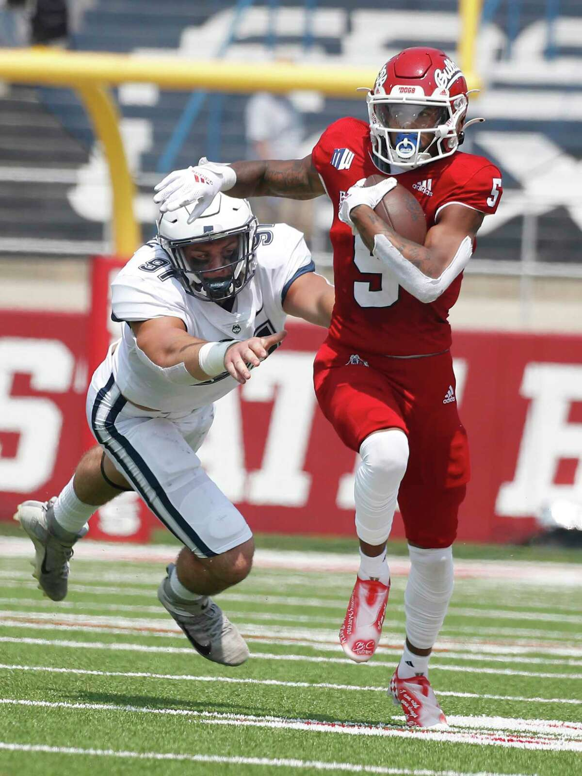 Fresno State wide receiver Jalen Cropper, right, runs past UConn's Collin McCarthy during the first half Saturday in Fresno, Calif.