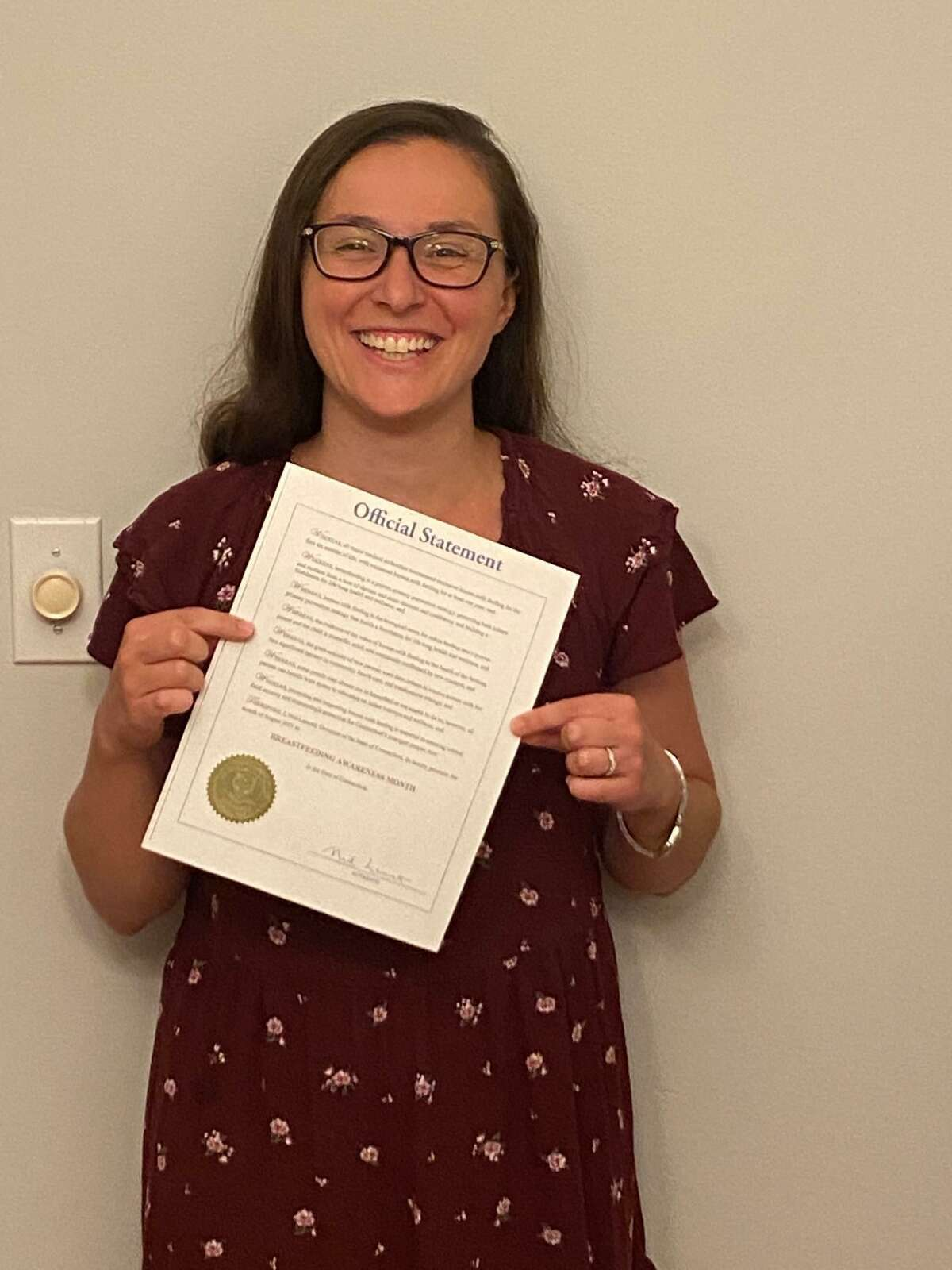 Jennifer Schindler-Ruwisch holds up a proclamation from Gov. Ned Lamont declaring August Breastfeeding Awareness Month.