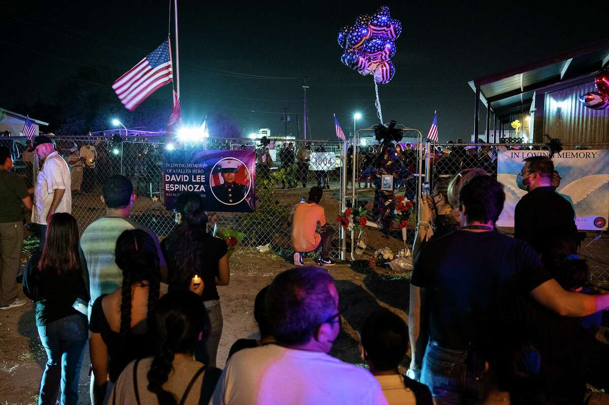 Mourners gather outside the home of the late Marine Lance Corporal David Lee Espinoza on Saturday, Aug. 28, 2021 during a candlelight vigil.