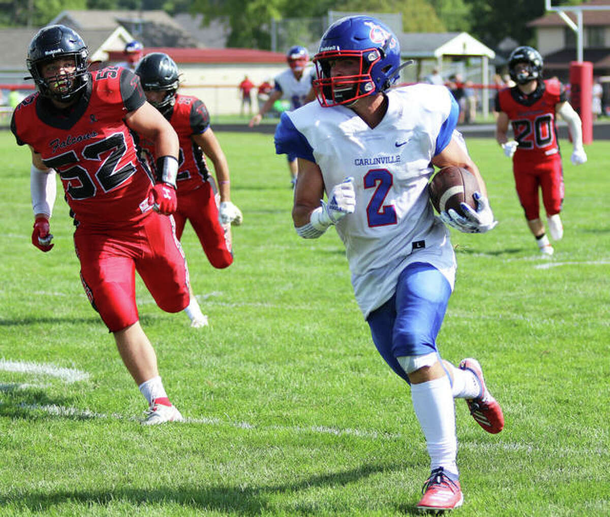 Carlinville's Carson Wiser (2) runs free for some of his 202 receiving yards from a school-record 13 catches while Gibson City's Brandon Mueller (52) gives chase on Saturday afternoon in Gibson City.