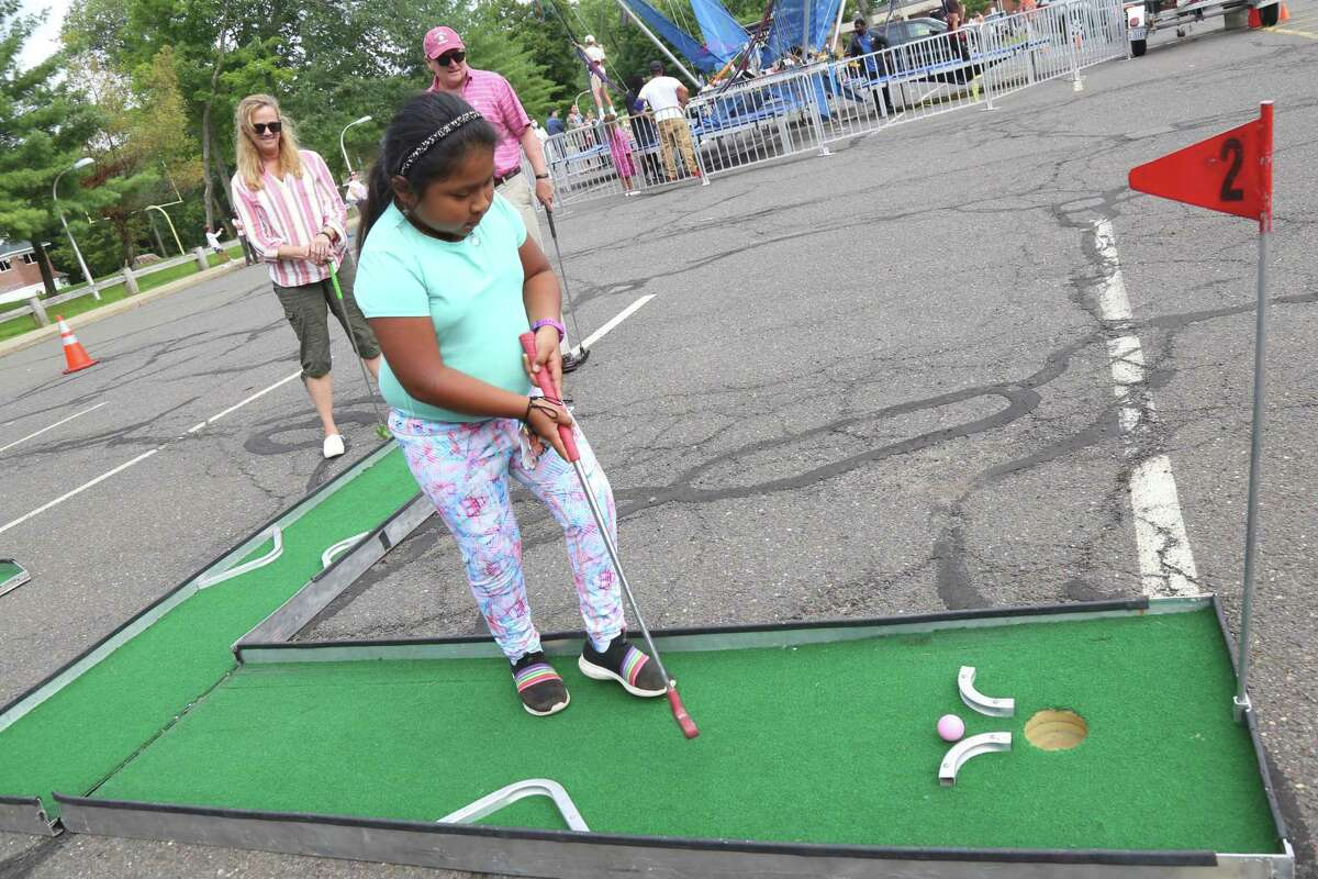 Anna Conroy, 8, of Ridgefield, puts on the mini golf course at Ridgefield Parks & Recreation Department's End of Summer Rec Party.