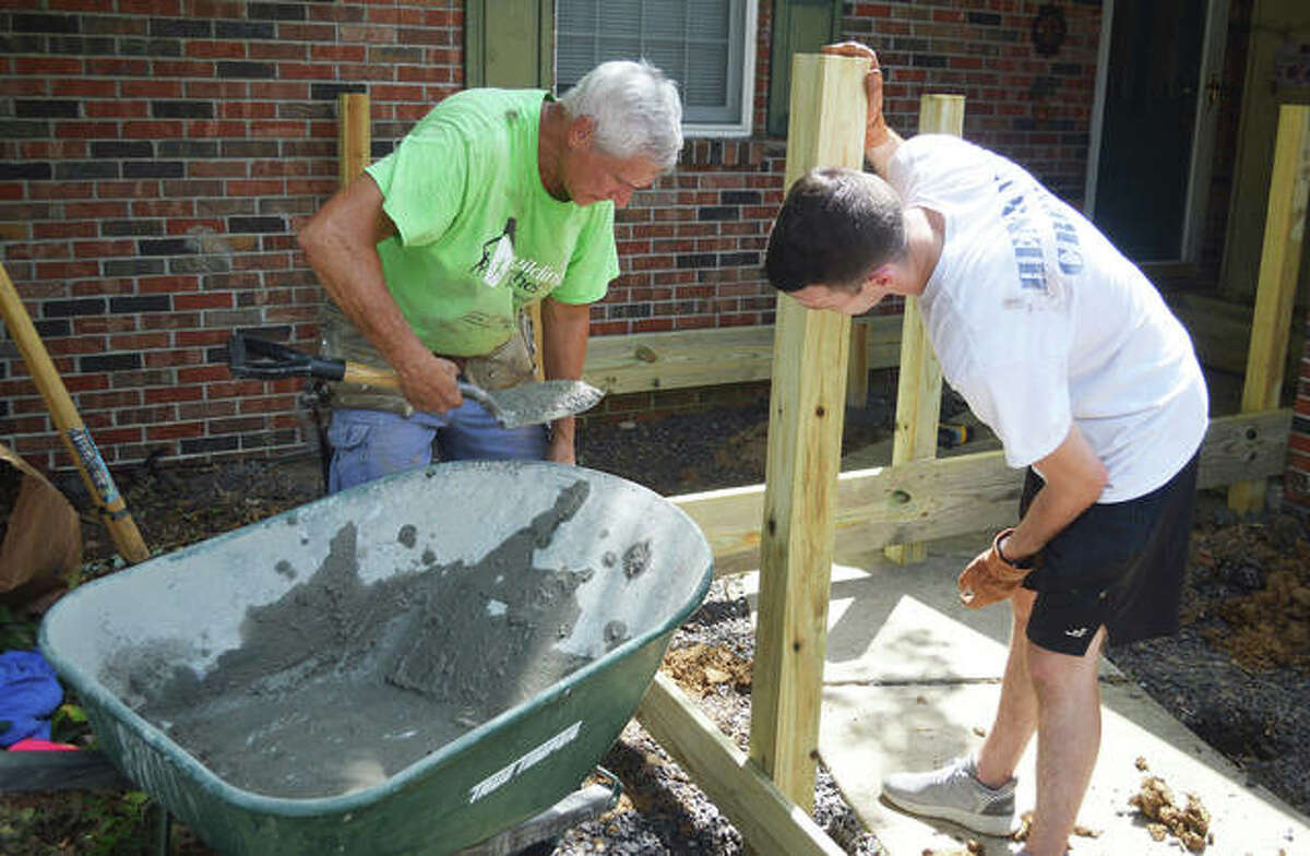 Chris Azar, left, president of Rebuilding Together Southwest Illinois, and Carson St. Andrews, a volunteer from Scott Air Force Base, put in a post for a wheelchair ramp during a project Saturday in Edwardsville.