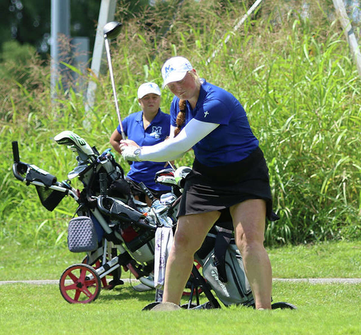 Marquette Catholic's Gracie Piar tees off on hole No. 10 to start the Blast Off Tourney on Aug. 21 at Spencer T. Olin. Teammate Audrey Cain, playing in the next foursome, watches the drive.