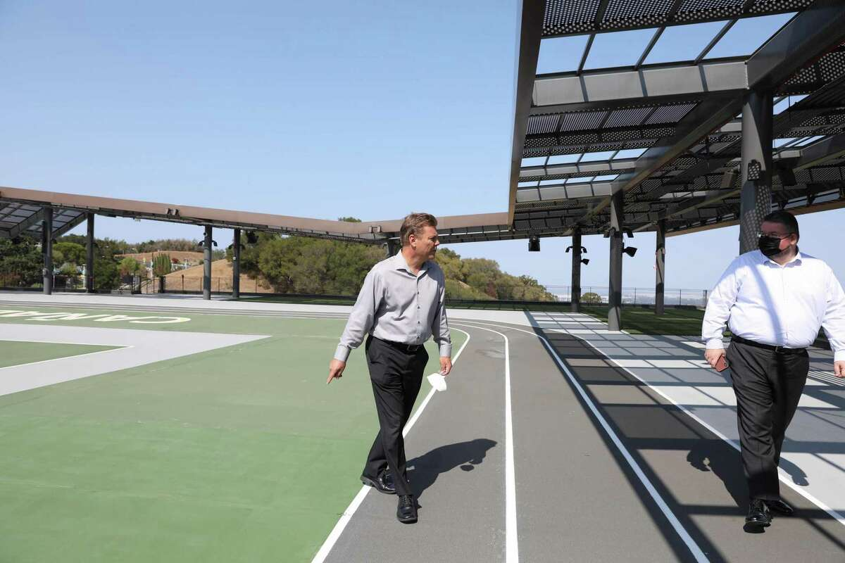 Michael Claire (left), chancellor of the San Mateo County Community College District, and Mitchell Bailey, chief of staff of the district, walk across the athletic area on the roof of the new million Kinesiology and Wellness Building in Redwood City.