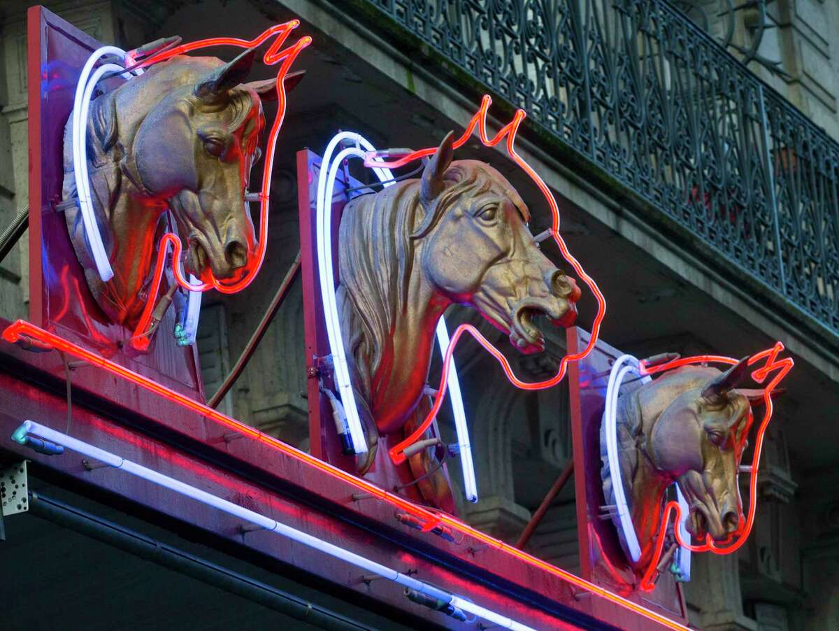 Three horse-head statues advertise a horsemeat butcher shop in Paris. Many countries condemn eating horses.