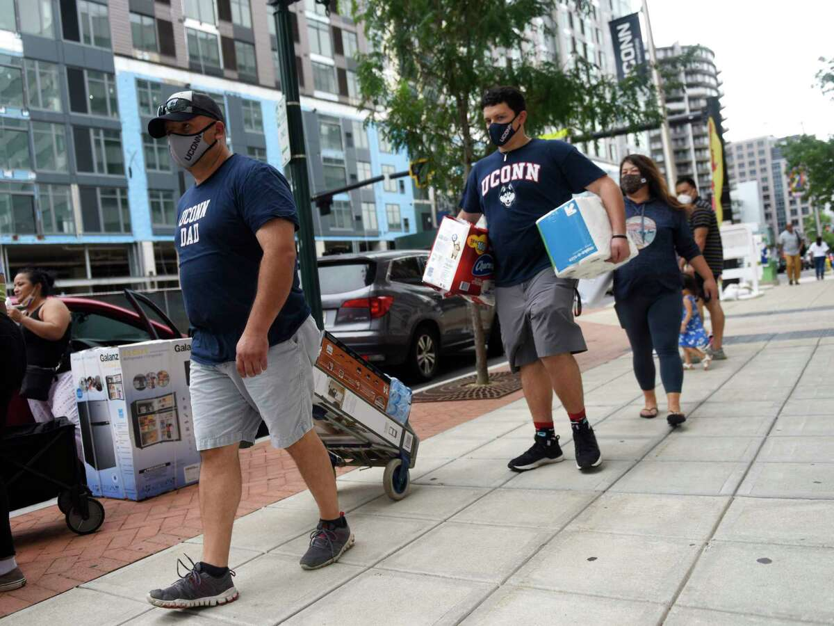 Incoming freshman Kyle Vasquez, center, carries his belongings with Sergio Vasquez, left, and Erica Johnson into the dorms at UConn Stamford campus in Stamford, Conn. Sunday, Aug. 29, 2021. Students returned to campus over the weekend before the start of the Fall 2021 semester.