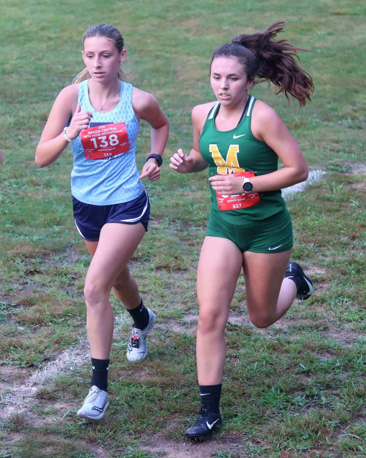 Brethren's Abby Kissling races alongside a runner from McBain after very little sleep the night before Saturday's race, after thunderstorms kept her dog, and by extension her, awake most of the night. (Robert Myers/News Advocate)