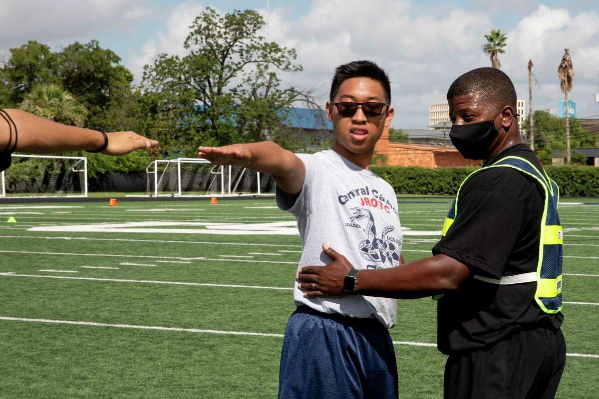 Retired Army Captain Dwayne Rhodes is the JROTC Senior Army Instructor at Central Catholic High School. During a physical training session, he helps Mathew Dolotina, Brigade IT officer, with his spacing for formal formations.