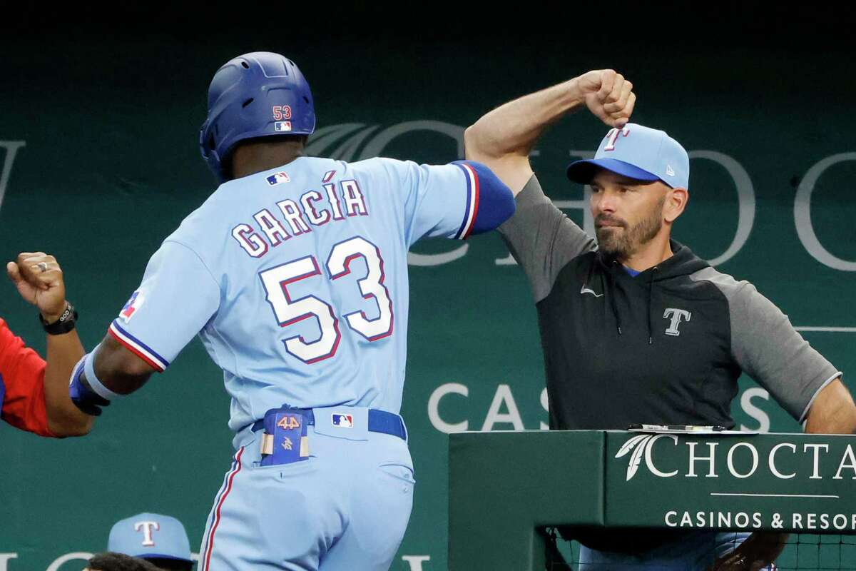 Texas Rangers' Adolis Garcia (53) is congratulated by manager Chris Woodward, right, after his grand slam against the Houston Astros during the fifth inning of a baseball game Sunday, Aug. 29, 2021, in Arlington, Texas. (AP Photo/Michael Ainsworth)