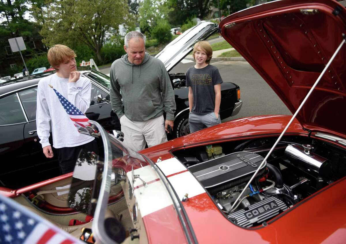 Greenwich's Alex Ercklentz looks at a Shelby Cobra with his sons Leighton, left, 15, and Ty, 11, at the Greenwich Police Department Scholarship Fund Benefit Car Show at Town Hall in Greenwich, Conn. Sunday, Aug. 29, 2021. It had originally been scheduled for Saturday, but was postponed a day out of an abundance of caution because of the stormy weather forecast. Admission was free, and all money raised went to benefit the Scholarship Fund, a nonprofit that awards scholarships to the children of active GPD officers for their undergraduate studies. In addition to the cars on display, the family-friendly event also featured a DJ, food trucks, a 50/50 drawing and more.