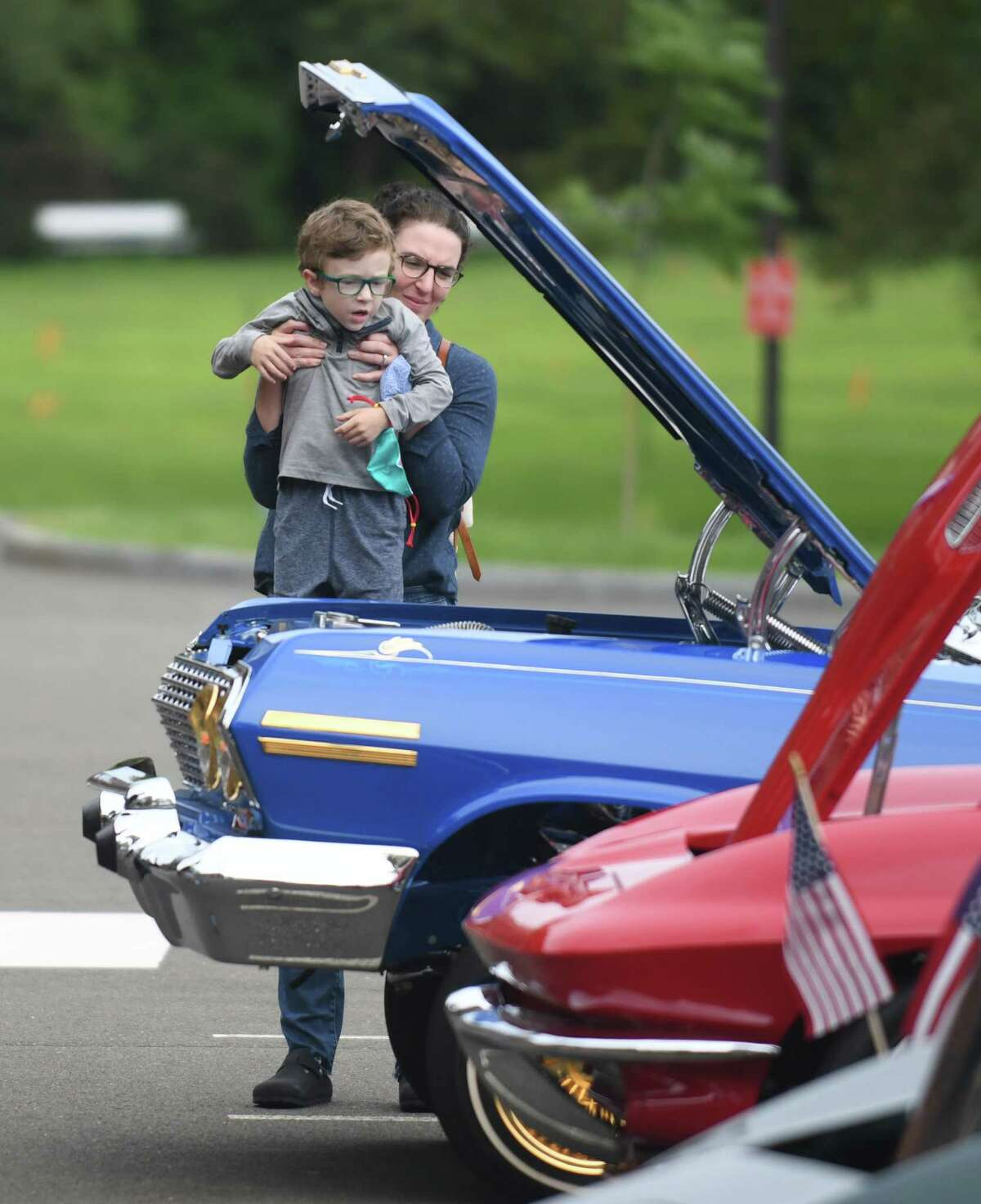 Greenwich's Kate Magaram lifts up her son, Bennett, 5, to see the engine of Chad McCollum's 1963 Chevy Impala, winner of the Best Engine Award, at the Greenwich Police Department Scholarship Fund Benefit Car Show at Town Hall in Greenwich, Conn. Sunday, Aug. 29, 2021. The free event included classic, antique, custom, and exotic cars, motorcycles, vintage fire trucks, and military vehicles.