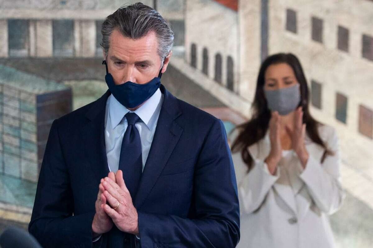 Gov. Gavin Newsom is applauded by Oakland Mayor Libby Schaaf during a visit to the city's Fruitvale neighborhood in May.