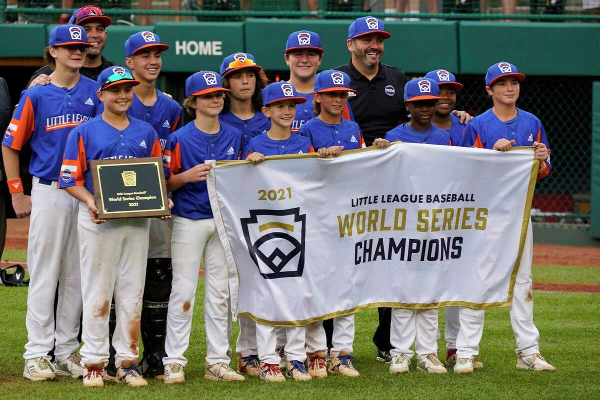 The Taylor, Mich., Little League team holds the Little League World Series Championship banner after defeating Hamilton, Ohio, in the championship baseball game in South Williamsport, Pa., Sunday, Aug. 29, 2021. (AP Photo/Gene J. Puskar)