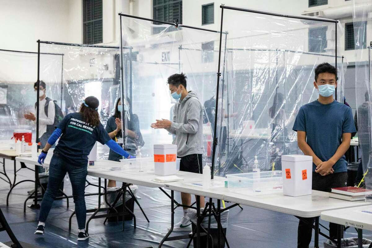 Students stand in separated stalls to conduct their own COVID-19 test at a mass testing site set up in UC Berkeley's Tang Center in Berkeley, Calif.