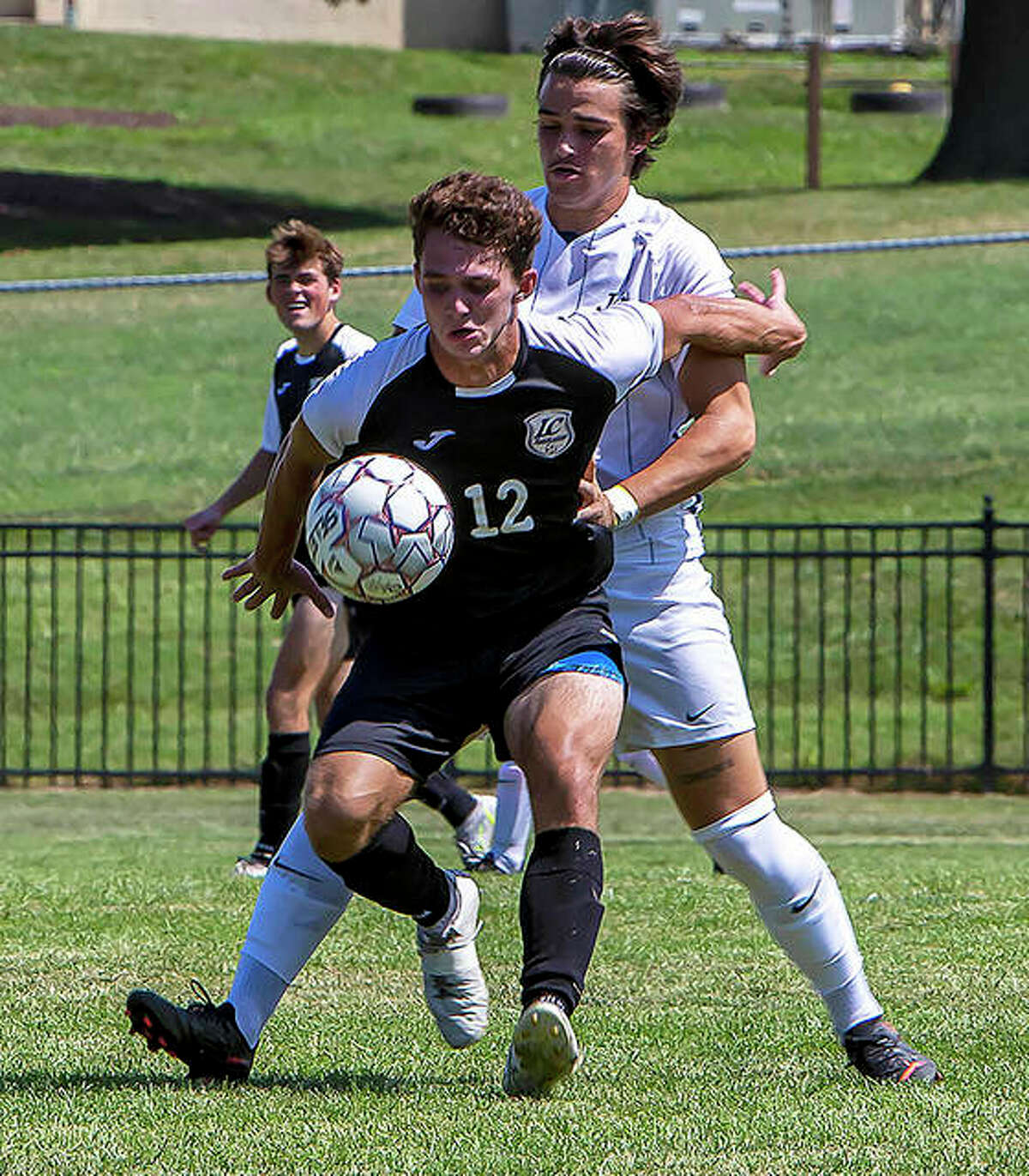 Lewis and Clark's Owen Sears (12) shields the ball from a Johnson County player Sunday at LCCC. Sears scored on a penalty kick for the Trailblazers, but they dropped their first game in three tries, 2-1.