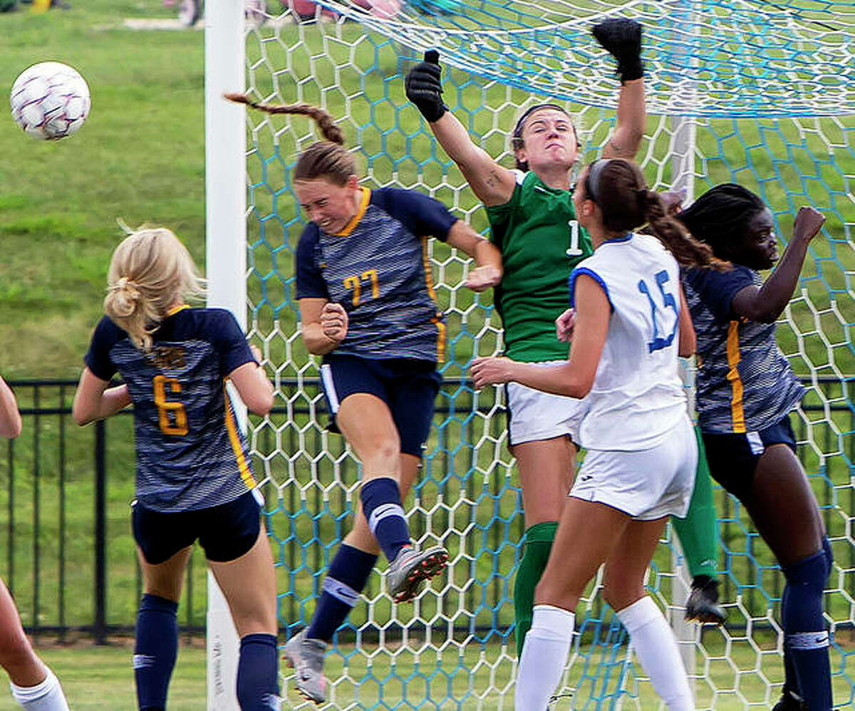 LCCC goalie Ally Cheeley (center in green) punches the ball away as Johnson County's Olivia Elliott (6) and Riley Porter (27) close in Sunday at LCCC. Also shown in LCCC's Carolynn Smith.