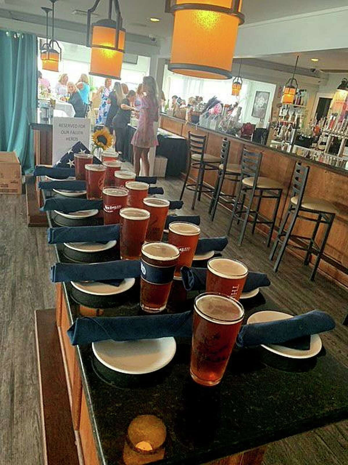 """Amid the table settings at Guilford Mooring Restaurant, poured pints of Thimble American Ale and an American flag folded for burial, was a sign that read, """"Reserved for our Fallen Heroes."""""""