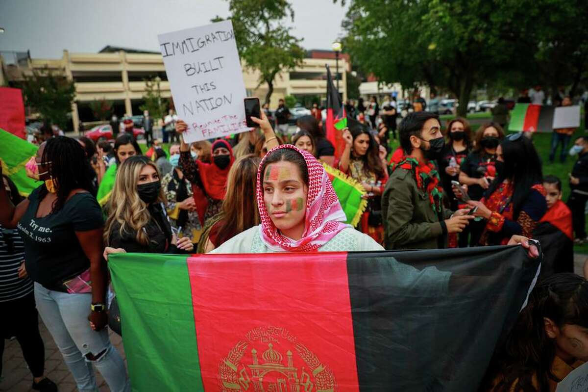 Ismail Safi, 12, holds a flag during a Hayward rally this month to support the people of Afghanistan after the recent Taliban takeover of the country. California is welcoming displaced Afghans.