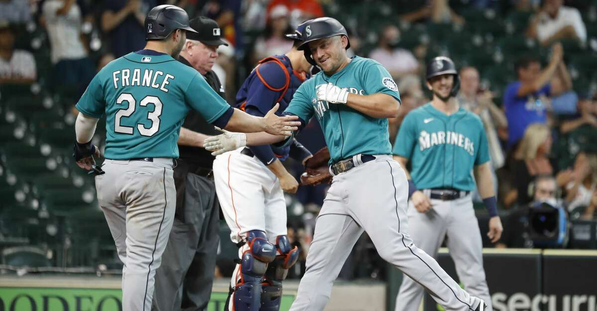 Seattle Mariners' Kyle Seager celebrates his three-run home run off Houston Astros' Ryne Stanek with Ty France during the eleventh inning of an MLB baseball game at Minute Maid Park, Sunday, August 22, 2021, in Houston.