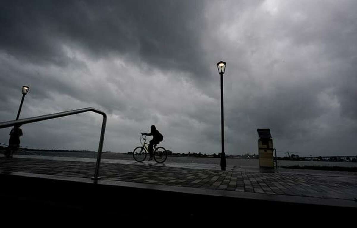 A man bikes along the Mississippi River near the French Quarter as the sun rises and the early effects of Hurricane Ida are felt, Sunday, Aug. 29, 2021, in New Orleans, La.