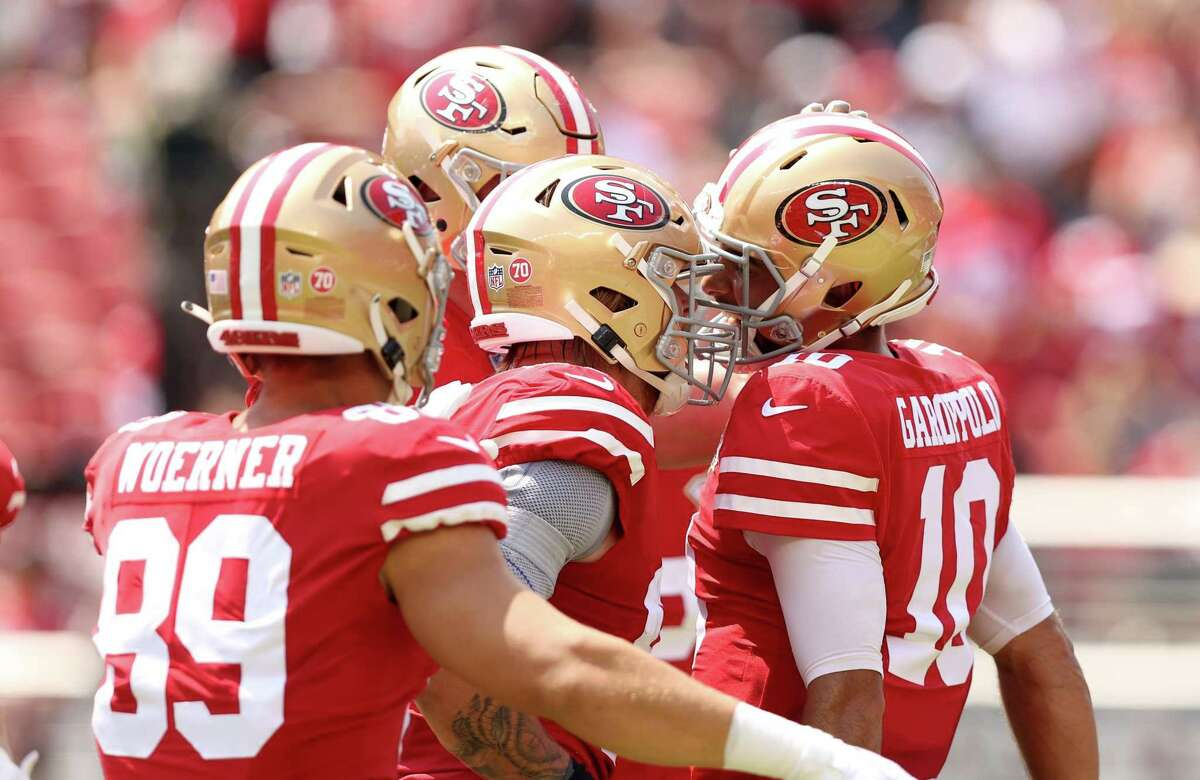 SANTA CLARA, CALIFORNIA - AUGUST 29: Jimmy Garoppolo #10 of the San Francisco 49ers is congratulated by teammates after he ran the ball in for a touchdown against the Las Vegas Raiders during their preseason game at Levi's Stadium on August 29, 2021 in Santa Clara, California. (Photo by Ezra Shaw/Getty Images)