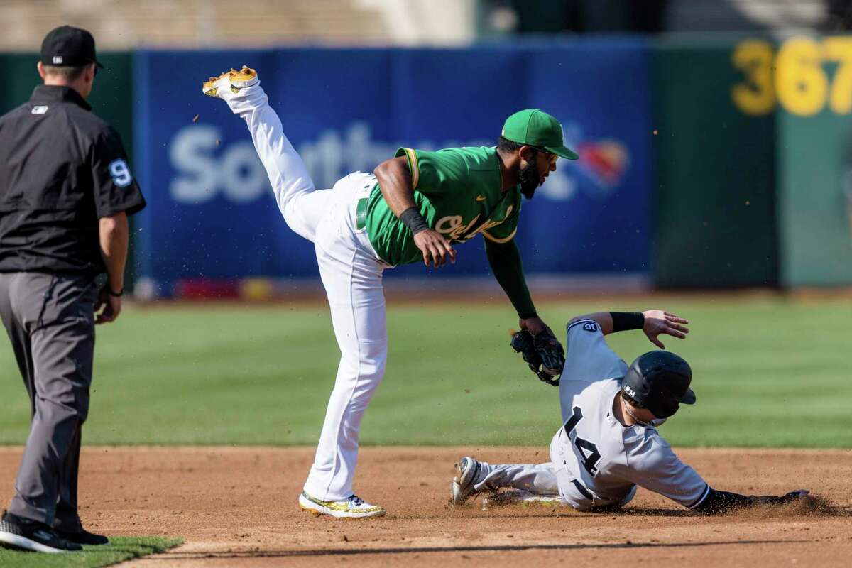 umpire Will Little, far left, watches Oakland Athletics shortstop Elvis Andrus, middle, tag New York Yankees' Tyler Wade (14) after a failed steal attempt in the third inning of a baseball game in Oakland, Calif., Sunday, Aug. 29, 2021. (AP Photo/John Hefti)