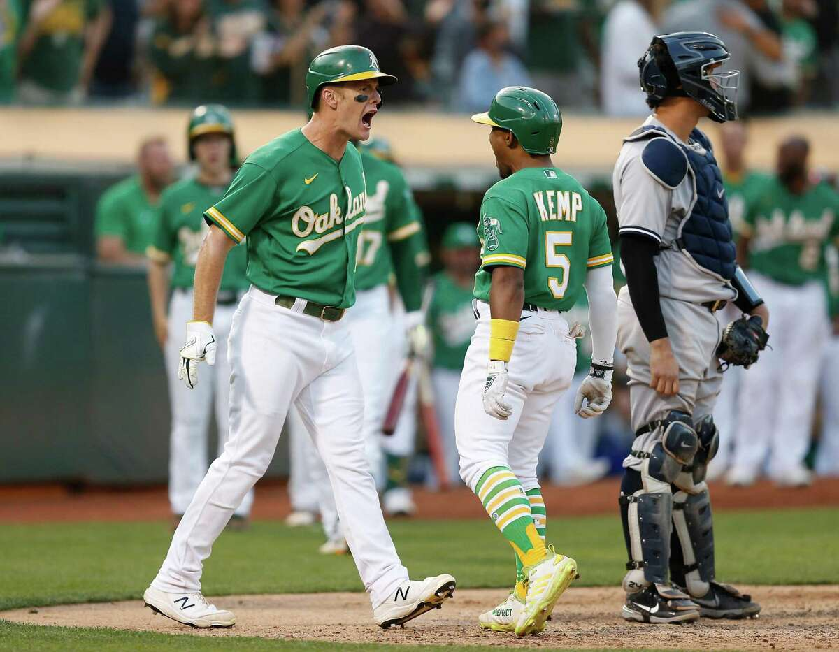 OAKLAND, CALIFORNIA - AUGUST 29: Tony Kemp #5 of the Oakland Athletics celebrates with Mark Canha #20 after hitting a two-run home run in the bottom of the eighth inning against the New York Yankees at RingCentral Coliseum on August 29, 2021 in Oakland, California. (Photo by Lachlan Cunningham/Getty Images)