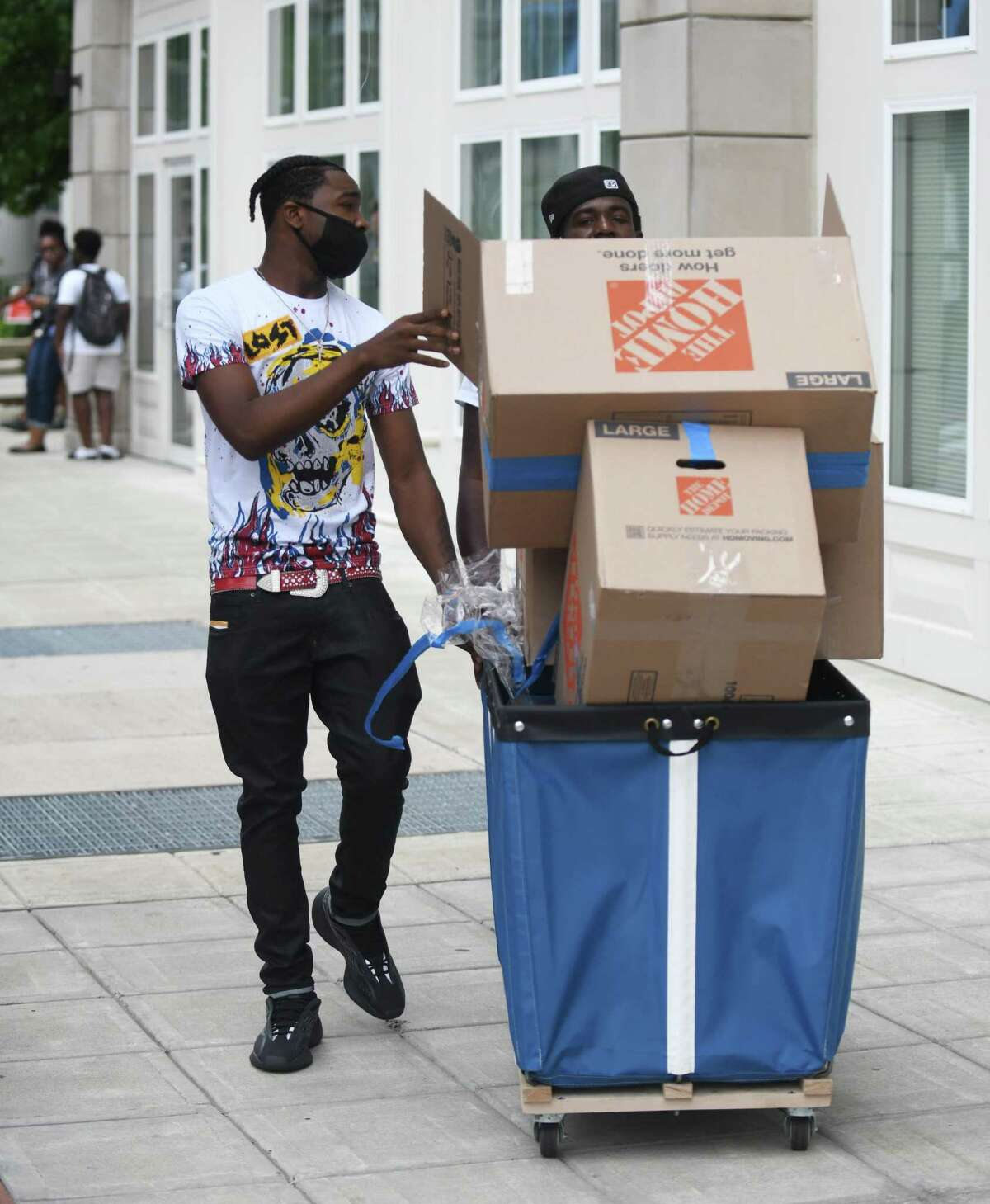 Incoming freshman Shakeemo Hill, left, gets help from his uncle Niko South moving boxes into the dorms at the UConn Stamford campus in Stamford on Sunday.