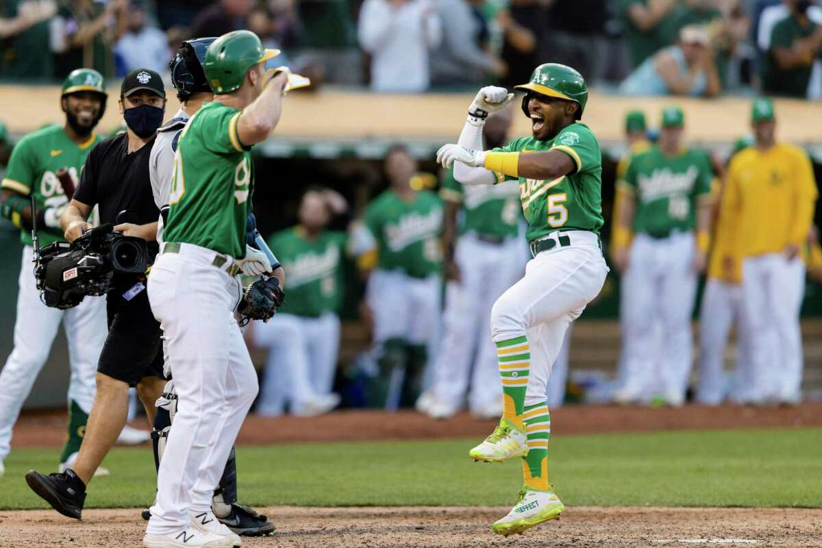 Oakland Athletics' Mark Canha, left, congratulates Tony Kemp (5) after he hit a two-run home run against the New York Yankees in the eighth inning of a baseball game in Oakland, Calif., Sunday, Aug. 29, 2021. The Athletics won 3-1. (AP Photo/John Hefti)