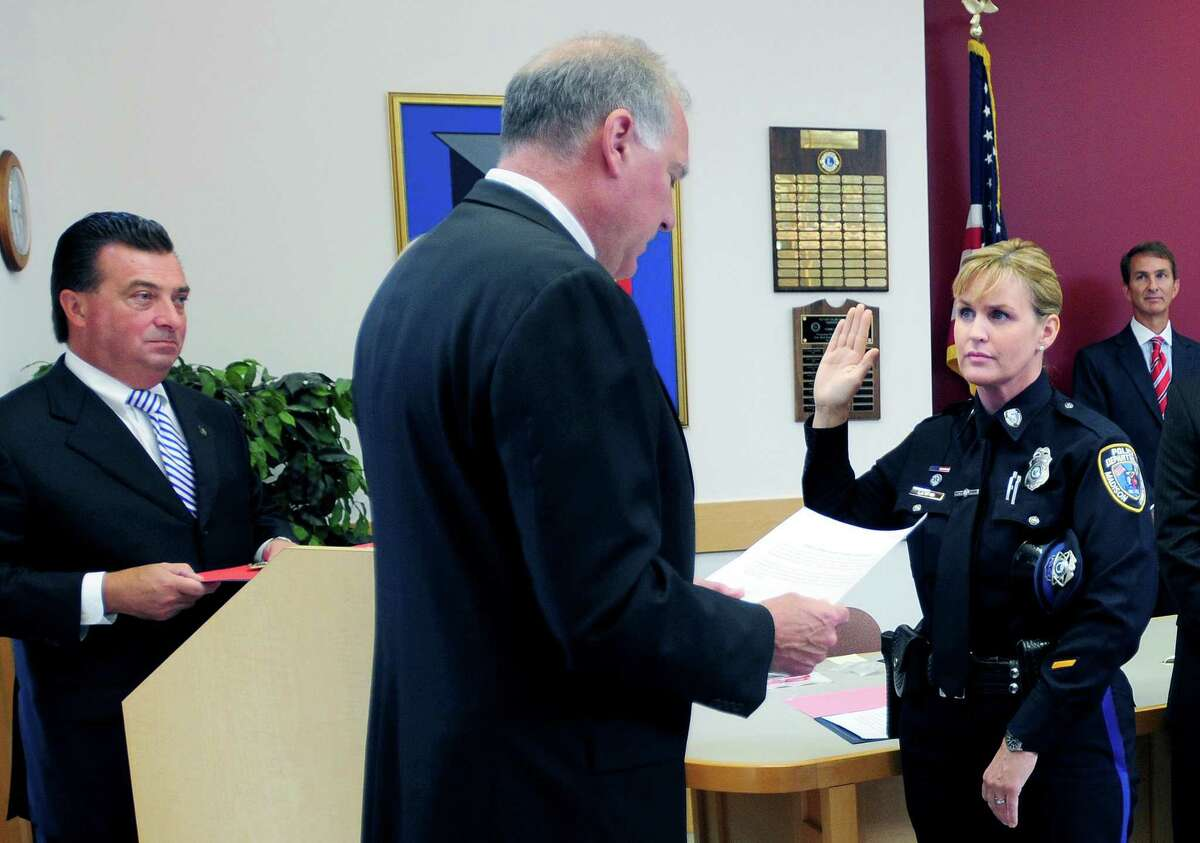 """From left, Madison Police Chief John """"Jack"""" Drumm watches Attorney General George Jepsen swear in Sgt. Kimberly Lauria at the Madison Town Offices in 2012."""