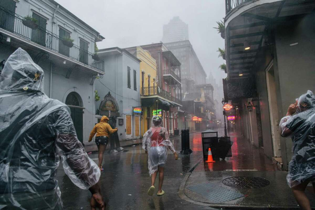 NEW ORLEANS, LOUISIANA - AUGUST 29: A group of people walk through the French District during Hurricane Ida on August 29, 2021 in New Orleans, Louisiana. Hurricane Ida made landfall earlier today and continues to cut across Louisiana. Hurricane Ida has been classified as a Category 4 storm with winds of 150 mph. (Photo by Brandon Bell/Getty Images) ***BESTPIX***
