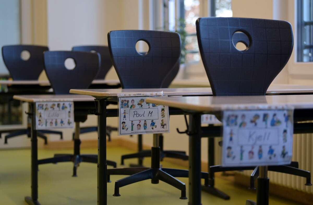 Chairs are placed on the school desks marked with first names in a classroom.