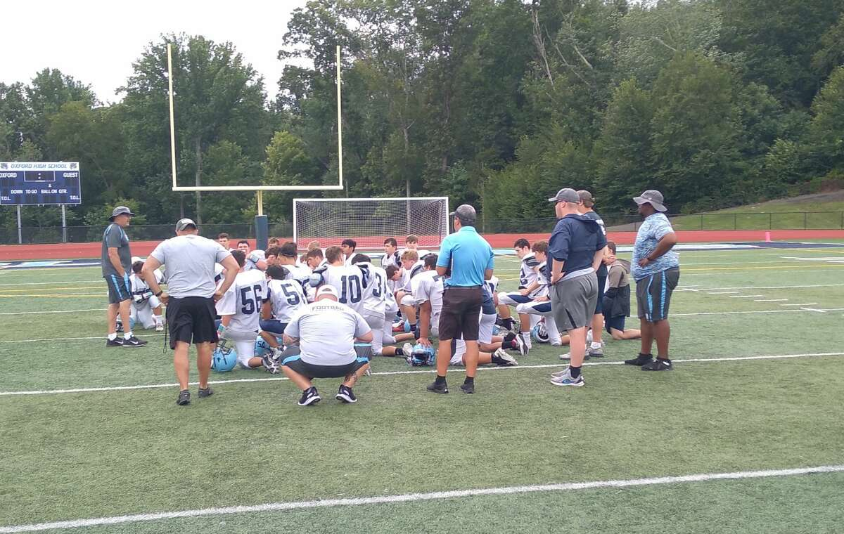 Oxford's football team huddles after a scrimmage at home in Oxford, Conn., on Aug. 28, 2021.