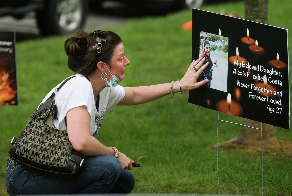 Andrea Curley, of New Milford, cries as she touches a memorial plaque to her best friend, Alexis Costa, of Danbury, at the inaugural Overdose Awareness Recovery Festival on the Green in New Milford, Conn. on Sunday, August 29, 2021. Costa died from a drug overdose earlier this year.