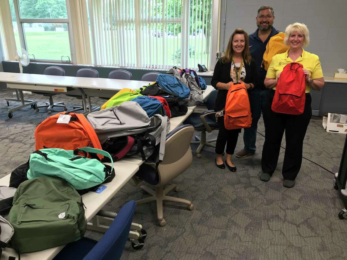 AT&T Michigan Pioneers on Friday presented 50 backpacks filled with school supplies to school administrators from Bullock Creek School District. Those pictured include Sen. Jim Stamas (middle) and Rep. Annette Glenn (right). (Photo provided)