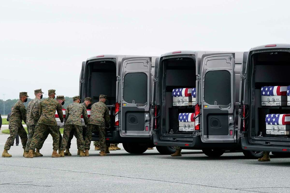 A Marine Corps carry team loads a transfer case containing the remains Marine Corps Lance Cpl. Dylan Merola, 20, of Rancho Cucamonga, Calif., at Dover Air Force Base, Del. President Joe Biden embarked on a solemn journey Sunday to honor and mourn the 13 U.S. troops killed in the suicide attack near the Kabul airport as their remains return to U.S. soil from Afghanistan. (AP Photo/Manuel Balce Ceneta)