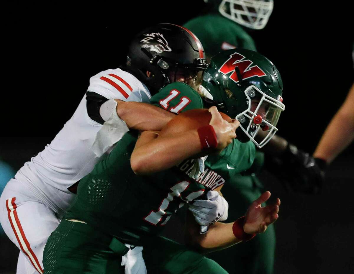 The Woodlands quarterback Mabrey Mettauer (11) is stripped of the ball by Langham Creek linebacker Logan Lake (15) during the third quarter of a non-district high school football game at Woodforest Bank Stadium, Thursday, Aug. 26, 2021, in Shenandoah.
