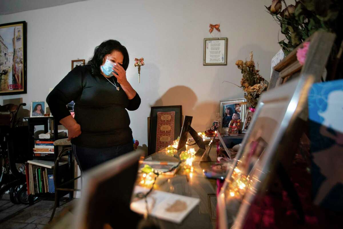 Rosie Peña reacts as she looks at the tribute she maintains to her daughter, Linda Pena Cordona, who was murdered in 2017, Sunday, Aug. 2, 2020, inside her Houston home. The family has now been waiting years for the accused killer to go to trial. Court documents show that Ricardo Olivarez pleaded guilty in early October and was taken back into custody, but the judge has reinstated his bond, and Olivarez is still out of custody waiting for trial. Harris County currently has a backlog of more than 1300 people awaiting trial on murder or capital murder charges.