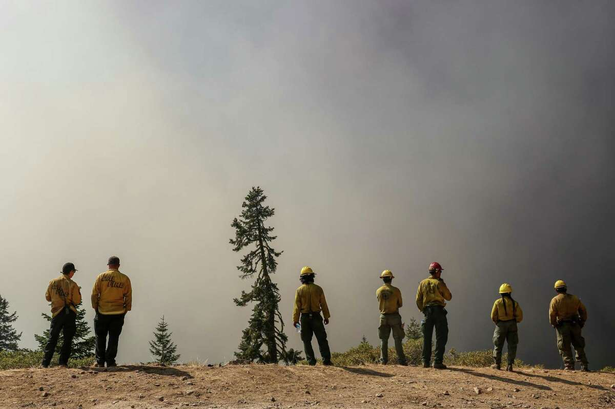 Crew members from Cal Fire and the U.S. National Forest Service monitor a large blaze from the Caldor Fire off of Mormon Emigrant Trail near Highway 88 near Strawberry, Calif. on Sunday, Aug. 29, 2021.