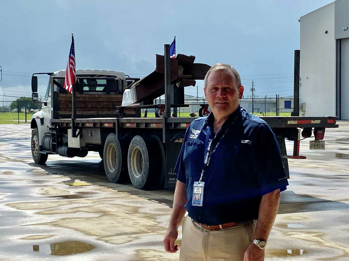 """Retired Lt. Gen. Doug Owens, president and CEO of the Lone Star Flight Museum, poses in front of an 11-foot section of a World Trade Center I-beam as it arrives at the museum in southeast Houston ahead of the """"Never Forget: Commemorating the 20th Anniversary of 9/11"""" exhibit, which opens Wednesday, Sept. 1."""