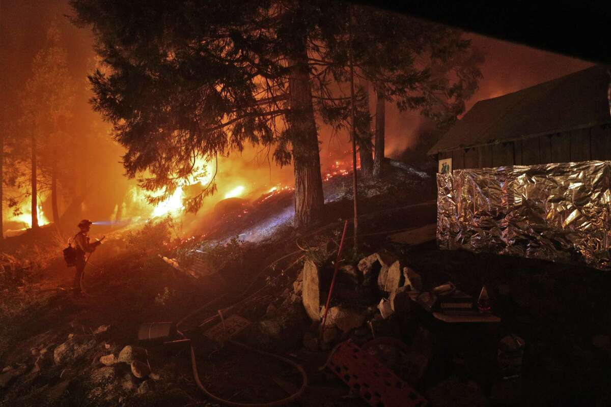 A firefighter monitors a backburn along Highway 50 next to a home that was partially wrapped in foil during the Caldor Fire in Strawberry (El Dorado County) last month.
