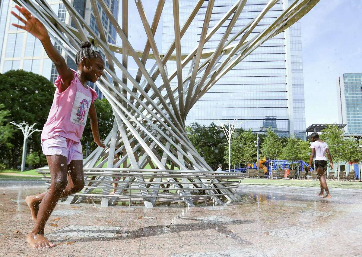Makiya Dowdell, 8, left, cools off with her cousin, Jazzy Knowles, 10, at Houston's Discovery Green Park on Monday, Aug. 2, 2021.