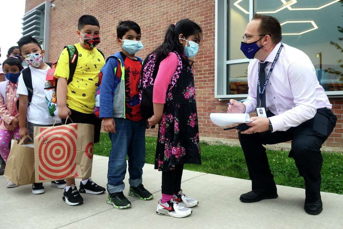Teacher Jeffrey Beckley greets students as they arrive for the first day of class at Jefferson Elementary School, on the Ponus Ridge STEAM Academy campus in Norwalk, Conn. Aug. 30, 2021.