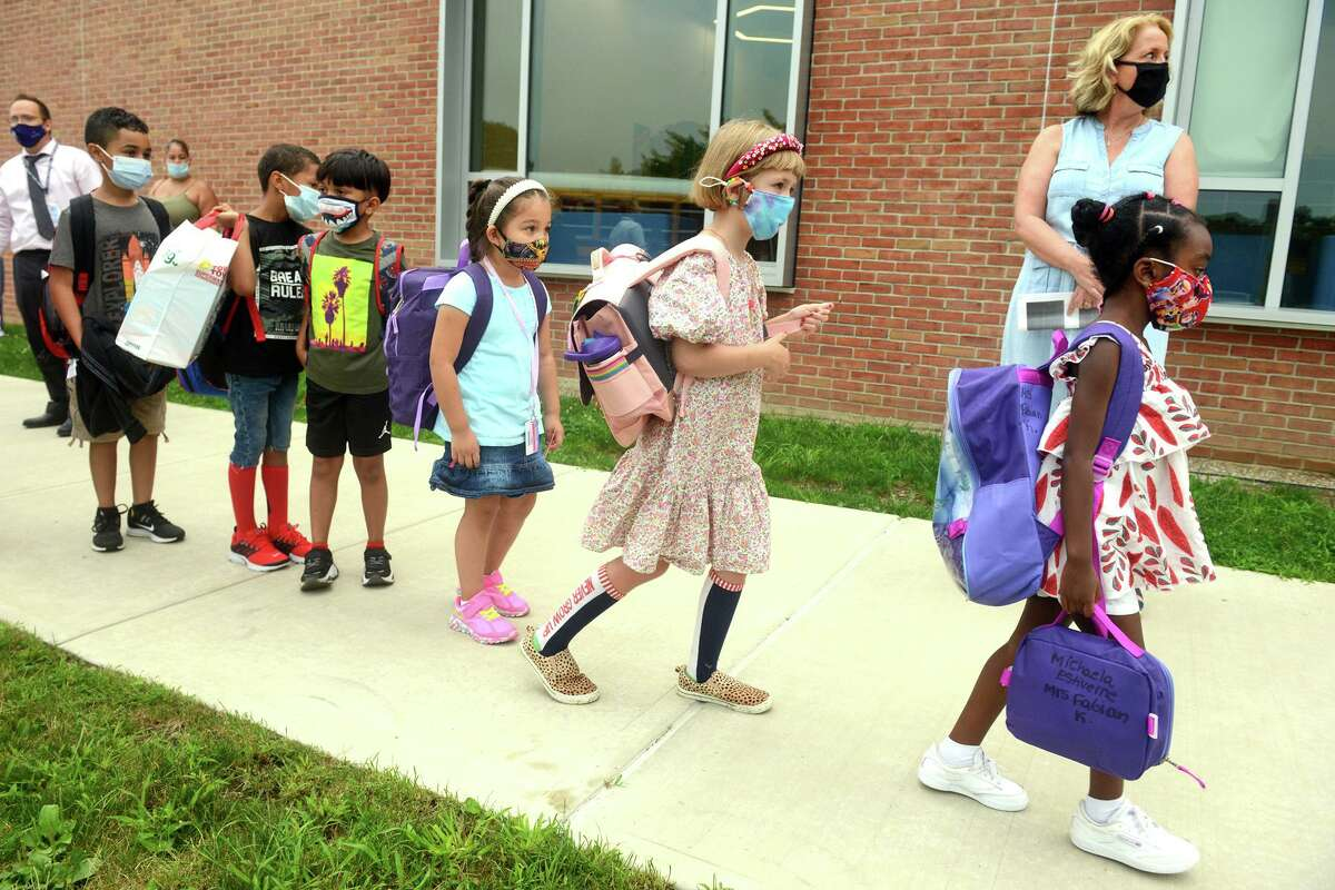 Students arrive for the first day of class at Jefferson Elementary School, on the Ponus Ridge STEAM Academy campus in Norwalk, Conn. Aug. 30, 2021. Students will be required to wear masks indoors through at least the end of September under a statewide mask mandate.