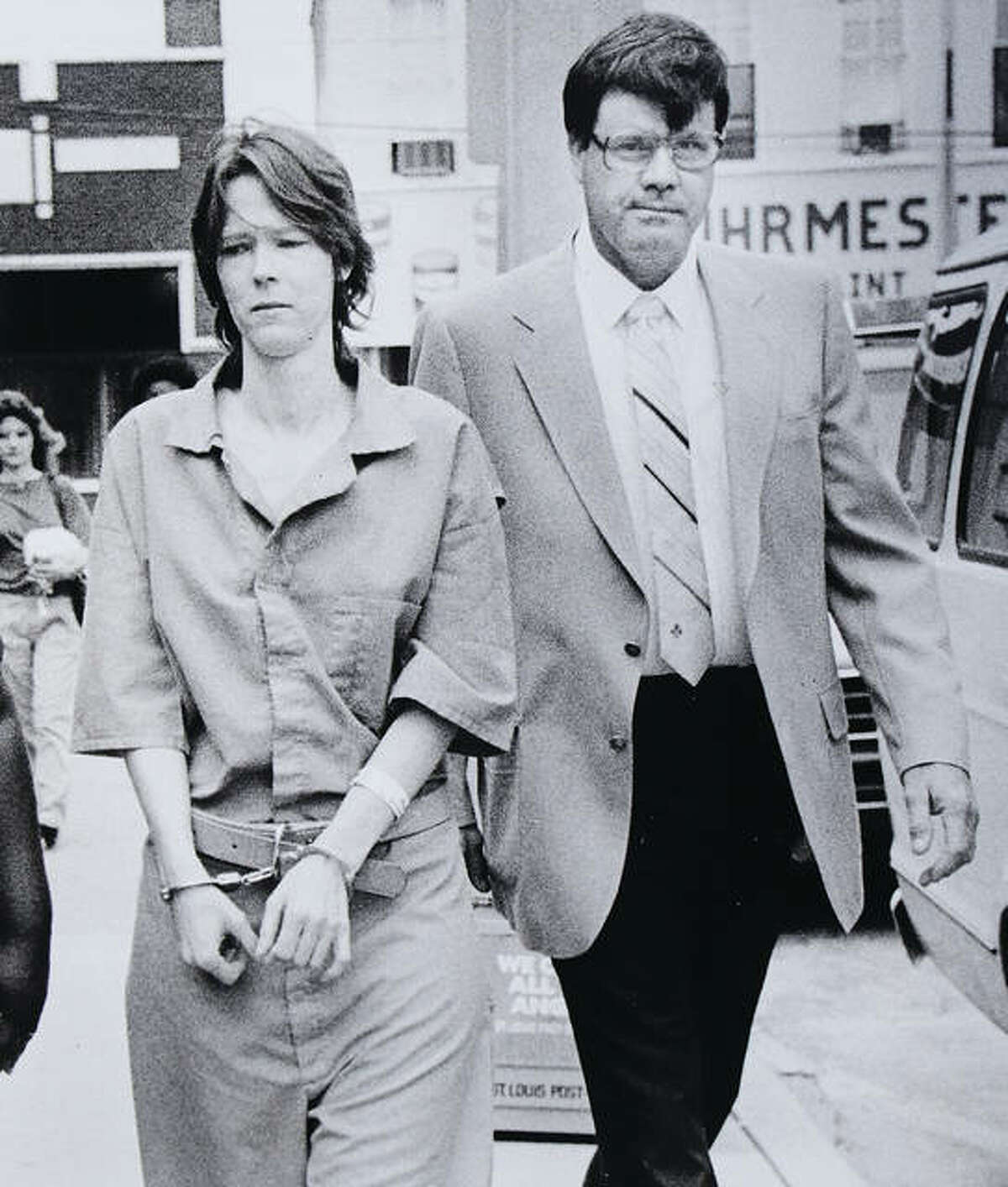 Wearing standard Madison County Jail clothing, Paula Sims is escorted by a deputy sheriff at the Madison County Courthouse. - John Badman|The Telegraph