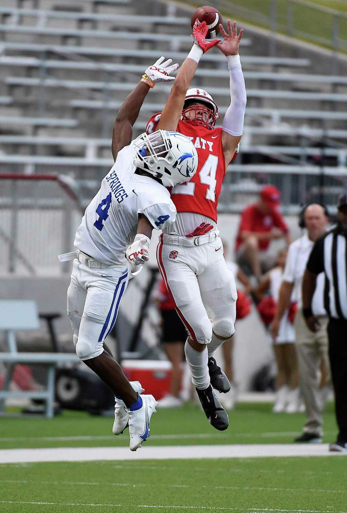 Clear Springs wide receiver Ky Woods (left) and Katy defensive back Hamilton McMartin leap for a pass during the first half of a high school football game last Friday in Katy.