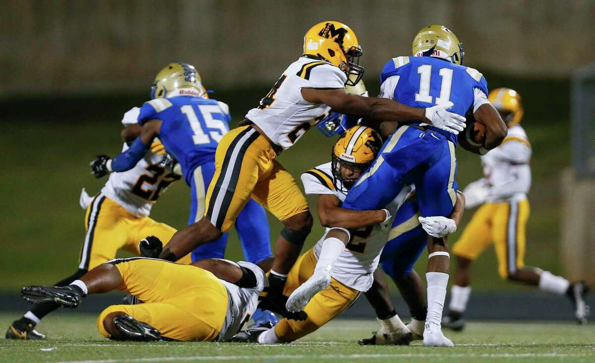 Fort Bend Marshall linebacker Jaylon Williams (24) and defensive back Christian Jackson (2) tackle Elkins Knights quarterback Jonathan Rhodes (11) during the second half of the game at Kenneth Hall Stadium Thursday, Oct. 1, 2020, in Missouri City , Texas.