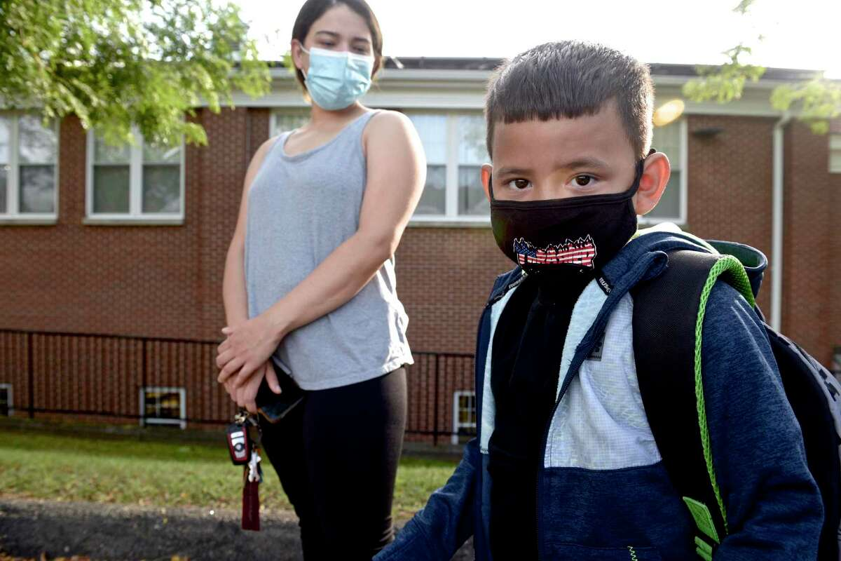 Dinan Mora, 5, of Danbury, waits with his mother Leydi Rosario at the Danbury Primary Center in Brookfield for the first day of kindergarten to begin. Monday, August 30, 2021, Brookfield, Conn.